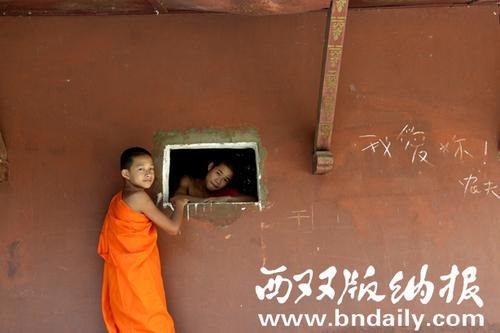 18-僧童通过佛寺里的窗口在窥视(摄于2013年4月勐海县勐遮镇)李植森
