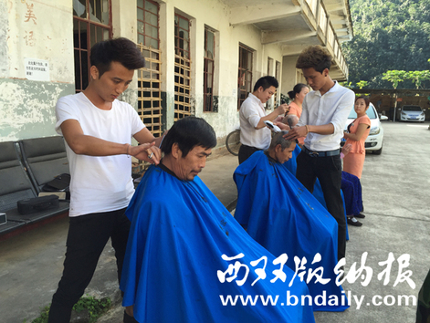 景洪市爱心大本营的爱心人士在为老人们剪发